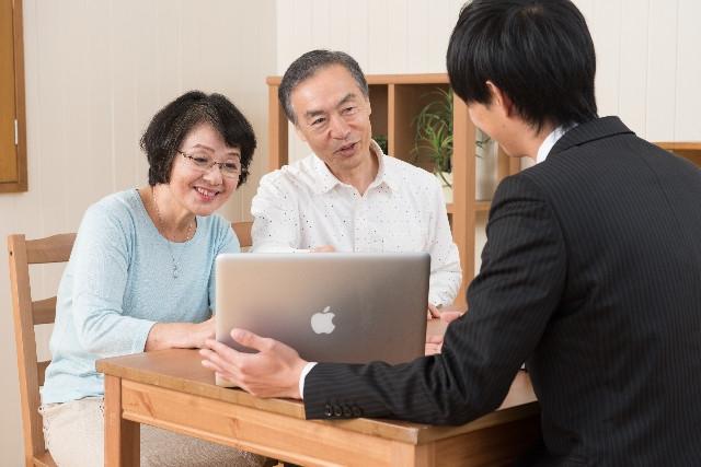 PCを見せながら説明するプランナーとそれを聞く夫婦